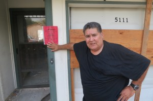 "Richard Rivera stands in front of a red sticker that marks his house as ""uninhabitable"" due to recent flooding. Photo credit: Mose Buchele"